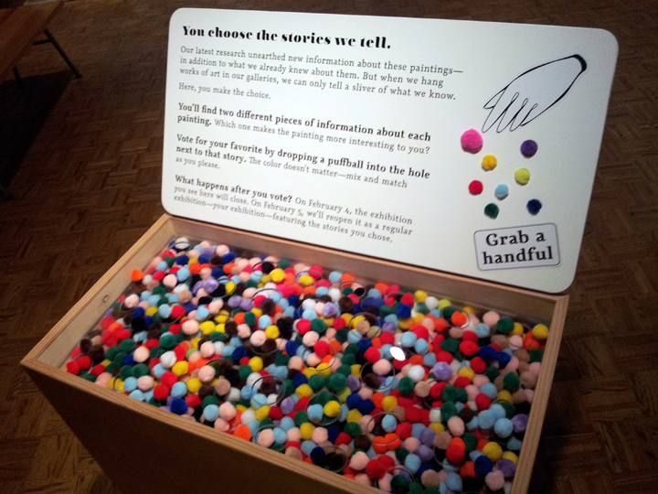 This bin of pompoms encouraged the visitor to vote via pompom on an exhibit label.