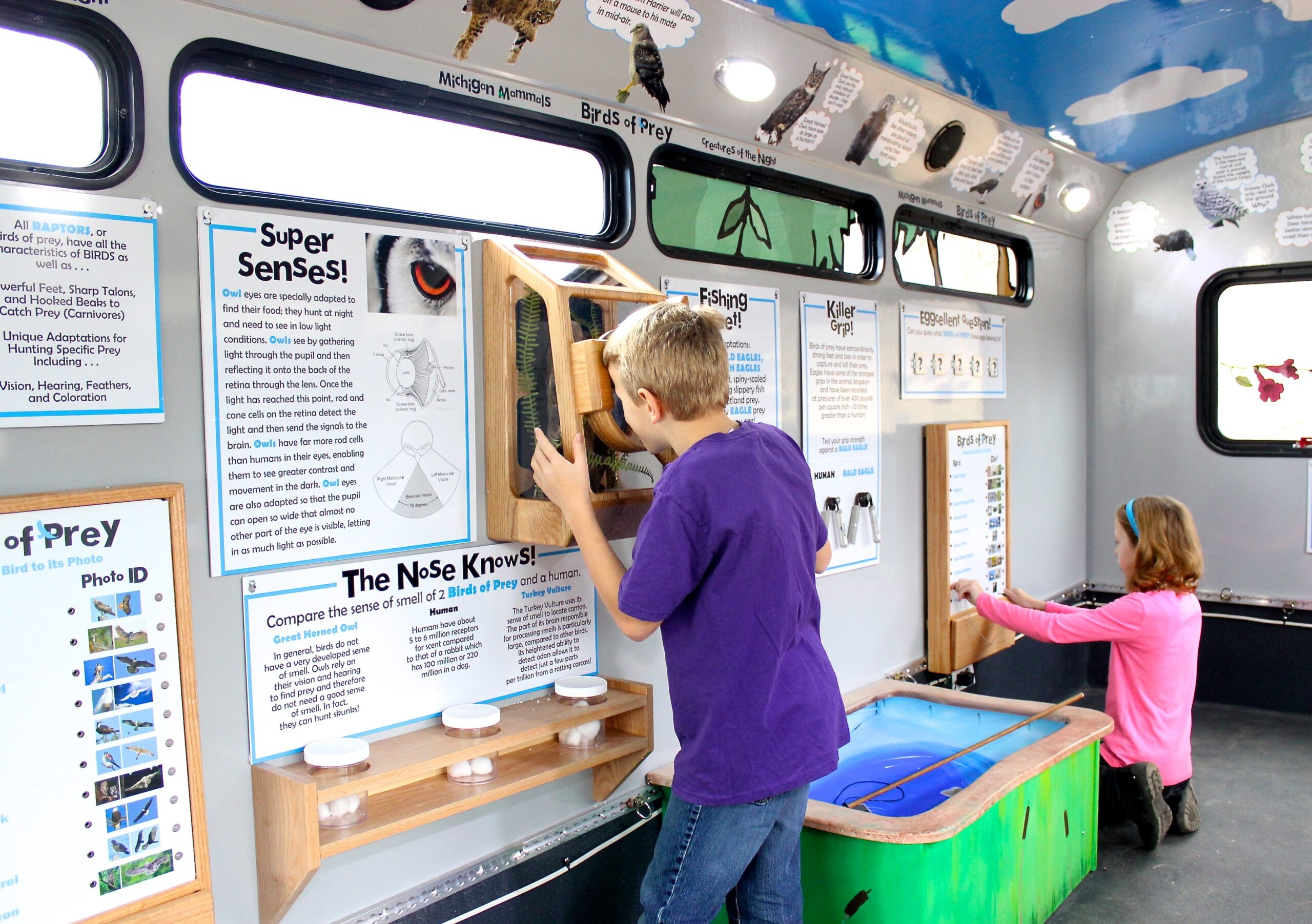 Inside the mobile exhibits bus, featuring Wildlife Quiz Boards and Night Vision Interactive.